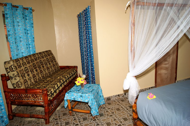 TYPICAL HUT INTERIOR SHOWING CORNER OF 4 POSTER BAMBOO AND LARGE BED SETTEE.