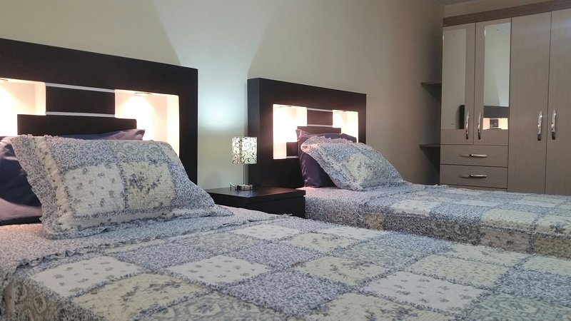 Bedroom 2 with two beds and half square, wardrobe, two bedside tables, lamps and other