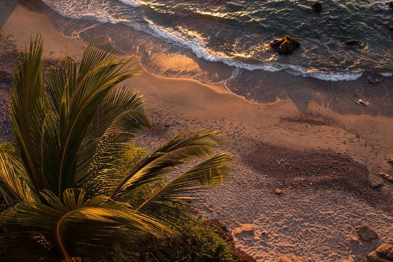 Ein Blick nach unten am Strand unterhalb von unserem Balkon bei Sonnenuntergang.