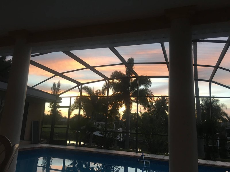 Seus pontos de vista do por do sol da piscina e va