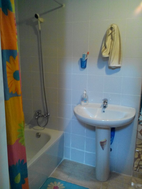 bathroom with shower, sink, toilet, towels, shampoo
