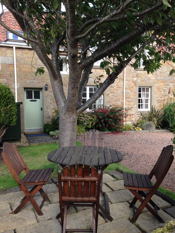 A frente do Smiddy Burn Cottage com área de pátio e cadeiras para 6.