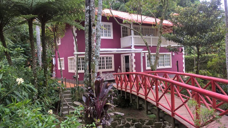 covered side porches with rocking and sofa access to the garden and the creek