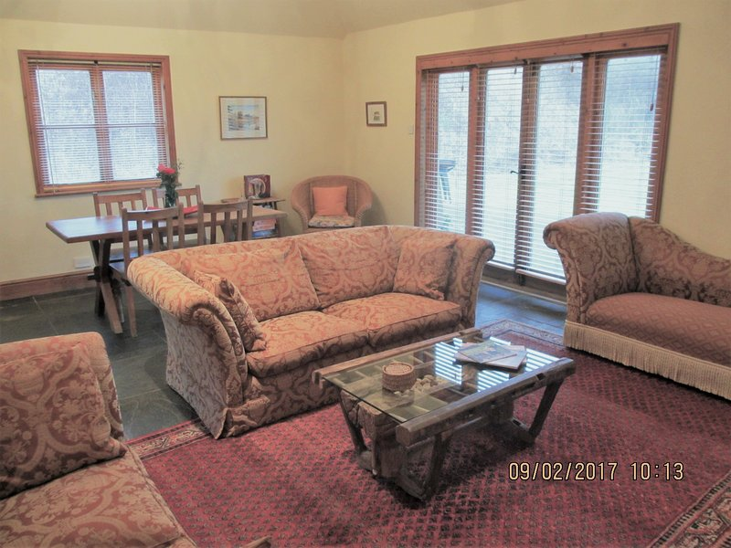 Two Comfortable Couches And Chaise Lounge Around An Antique Coffee Table  And Large Woodburner