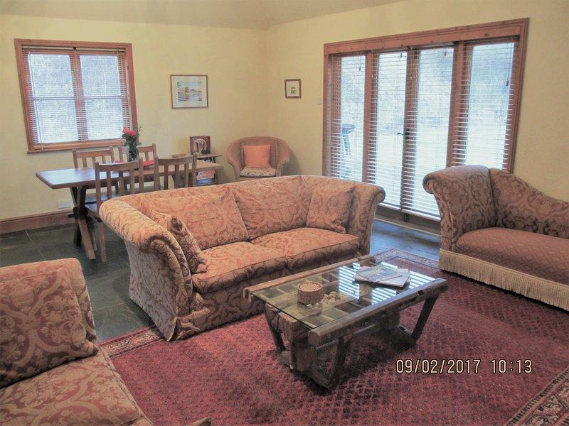 Twee comfortabele banken en chaise lounge rond een antieke salontafel en een grote houtkachel