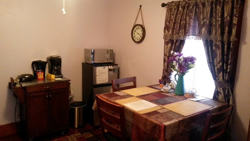 Kitchenette. Frigorífico pequeno, microondas, cafeteira, ketle elétrico de água, gravador de balcão único para a cozinha simples