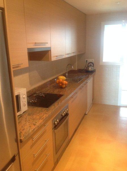 Cuisine équipée avec comptoirs en granit, Four / Hob, Lave-vaisselle et réfrigérateur-congélateur.