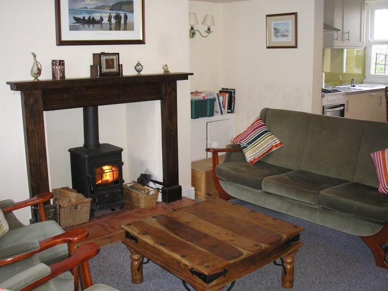 Lounge with woodburning stove is open through to the litchen.