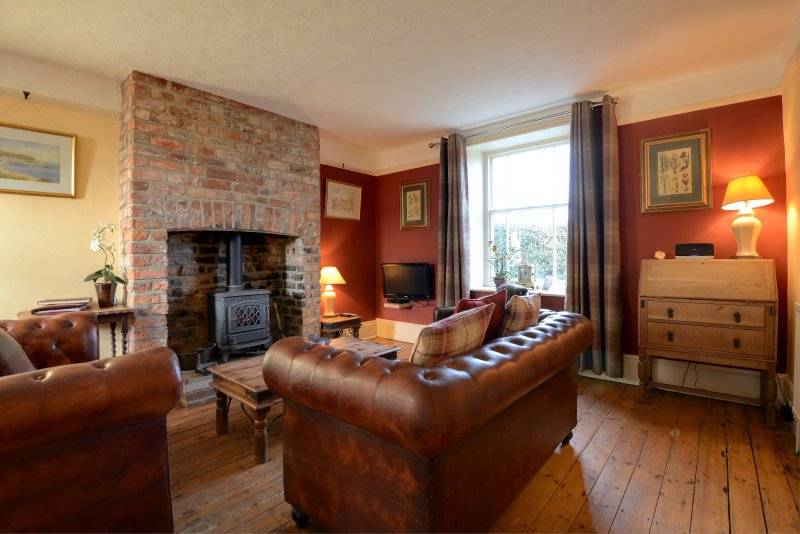 Chapel Cottage large family lounge with ample seating and big squishy cushions and gas stove