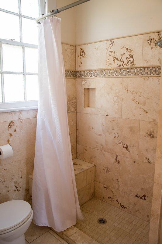 Salle de bains latérale gauche avec douche en travertin