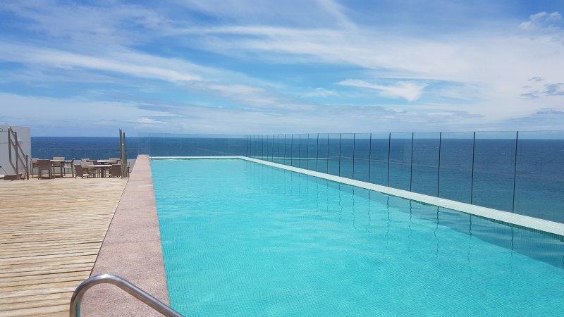Terraço com piscina e vista para o mar.