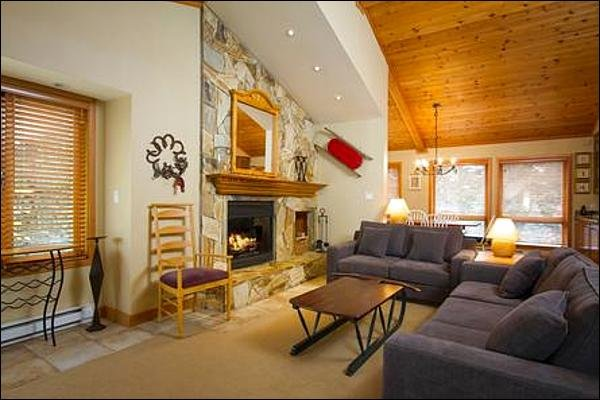Gorgeous Renovated Living Room with High Ceilings and Stone Fireplace