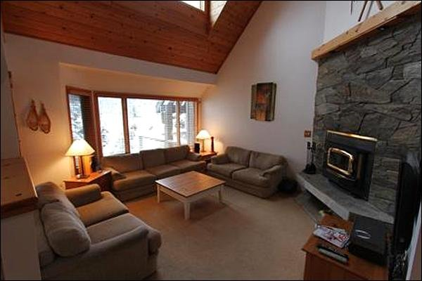 Luxuosa área de estar rebaixada com lareira a lenha e TV de tela plana.