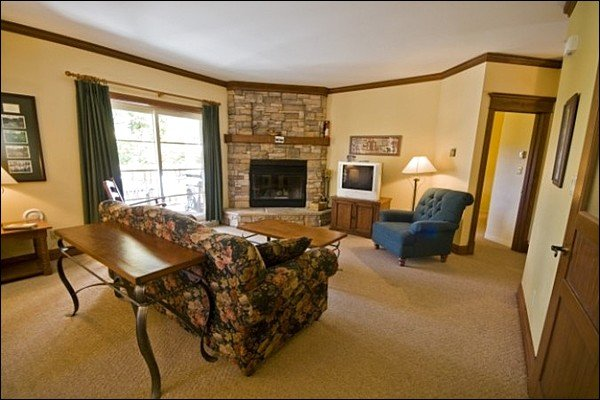 The Cozy Living Area Featuring a Stone Fireplace