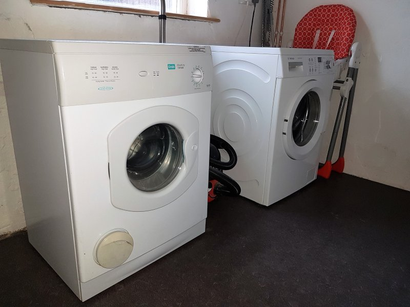 utility room with washing machine, tumble dryer , ironing board and iron