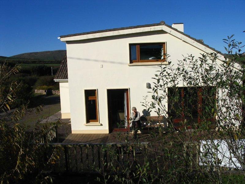 Retour de la maison avec des portes de chambre ouverte et salon sur grande terrasse.