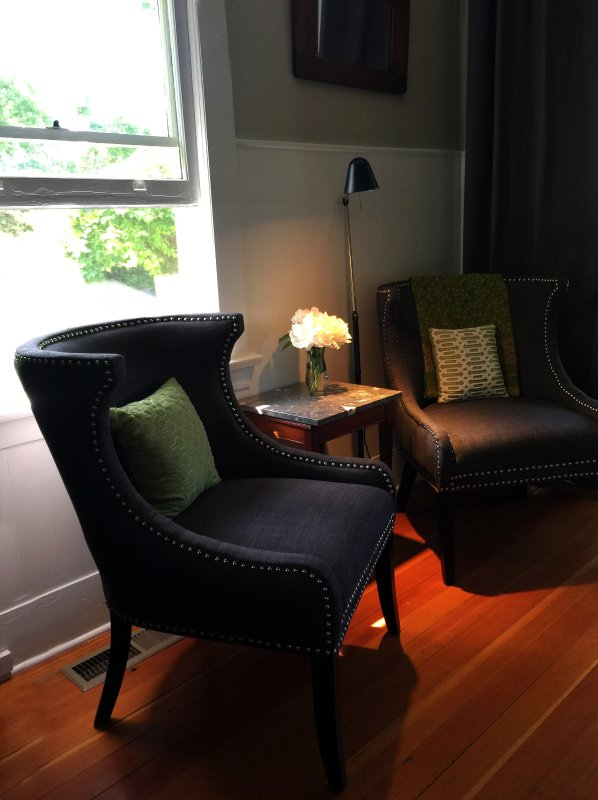 Two Oversized Chairs Offer a Comfortable Sitting Area. There is a Larger Table Between Them Now.