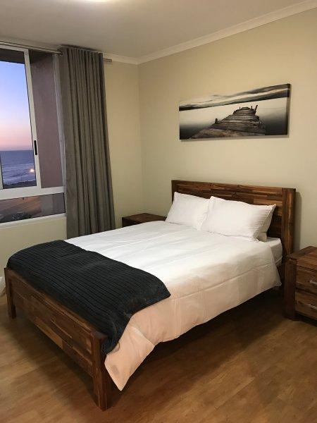 Main bedroom with queen size bed-build in cupboards-ensuit bathroom- bath-Basin- toilet. Ocean view