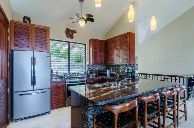 Luxurious, well appointed kitchen with stunning Honduran granite bar and counter
