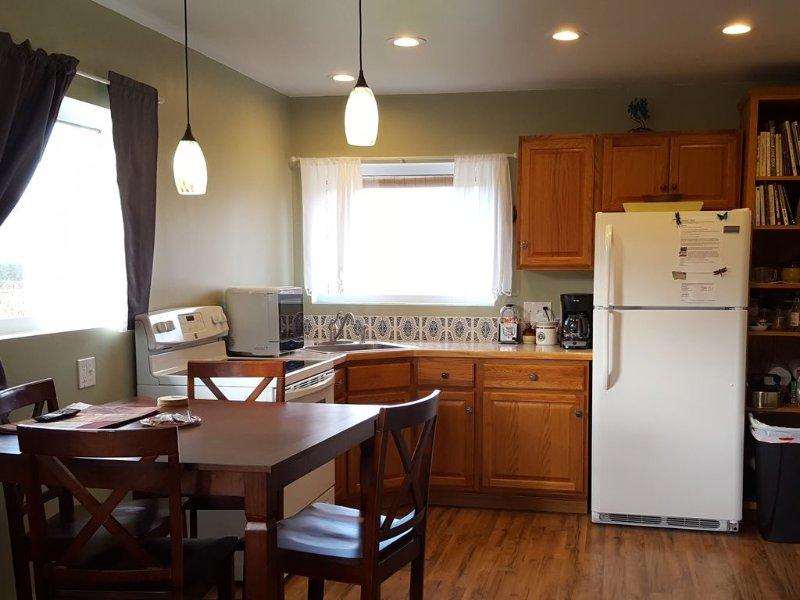 Köket är utrustat med porslin, bestick och köksredskap; den har en elektrisk spis, kylskåp