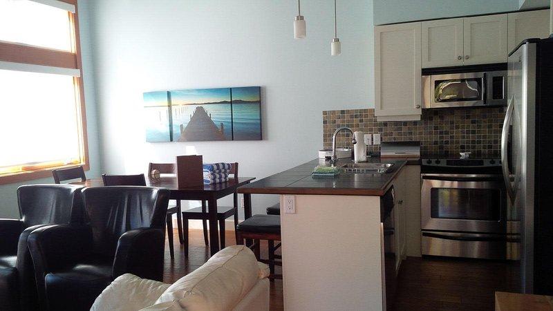Condomínio de plano aberto com uma cozinha totalmente equipada, sala de jantar e sala de estar