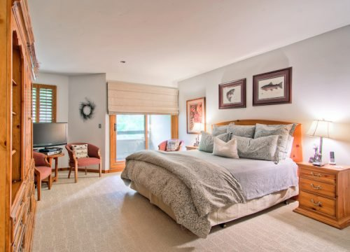 The light and airy master suite features a small seating area and balcony.