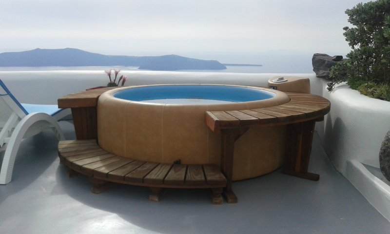 outdoor hot jet tub Jacuzzi with view to the sea, sunset, caldera