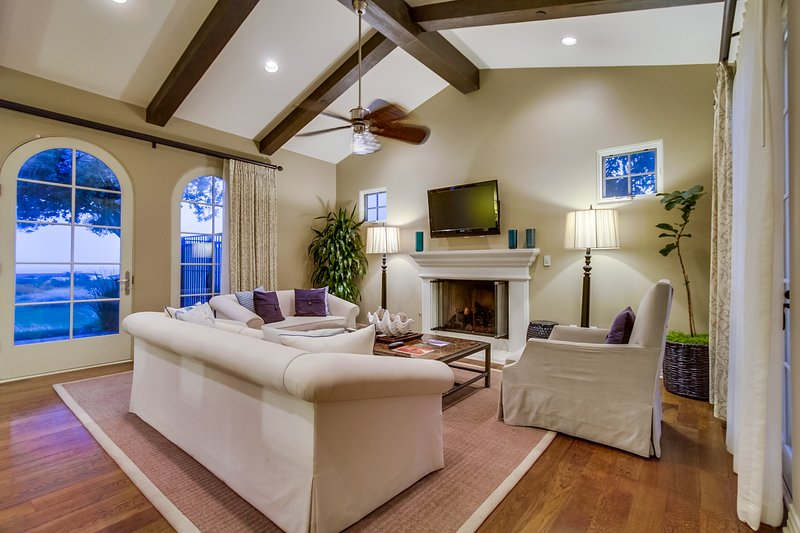 The living room has comfortable seating in front of a fireplace and flat panel TV.