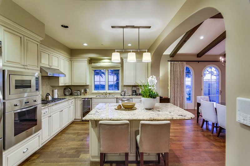 The gourmet kitchen include marble counters and a kitchen island with additional bar stool seating.