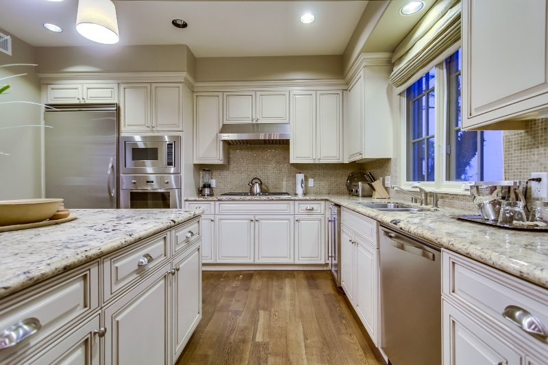 The kitchen features lots of  cabinet and storage, and place settings for 8.