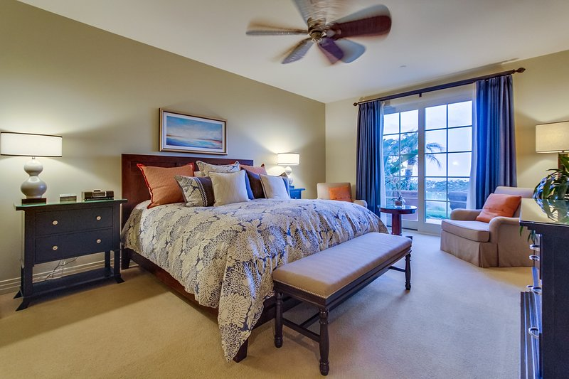The master bedroom has a king sized bed with designer pillows and bedding.