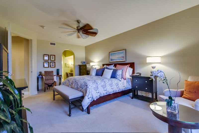 The spacious master bedroom includes a sitting area and ceiling fan.