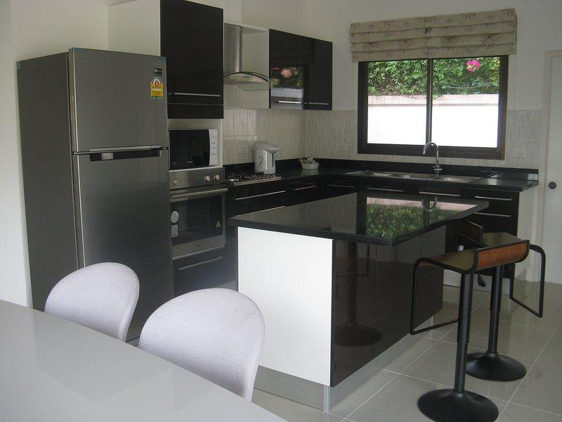 Cucina, dotato di un forno elettrico, piano cottura a gas, estrattore doppio lavello e scolapiatti, bar per la colazione.