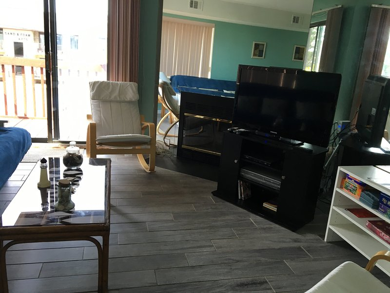 Main floor living room has 42' flat screen TV w/ HBO, wifi, large deck, DVDs, books, & games.