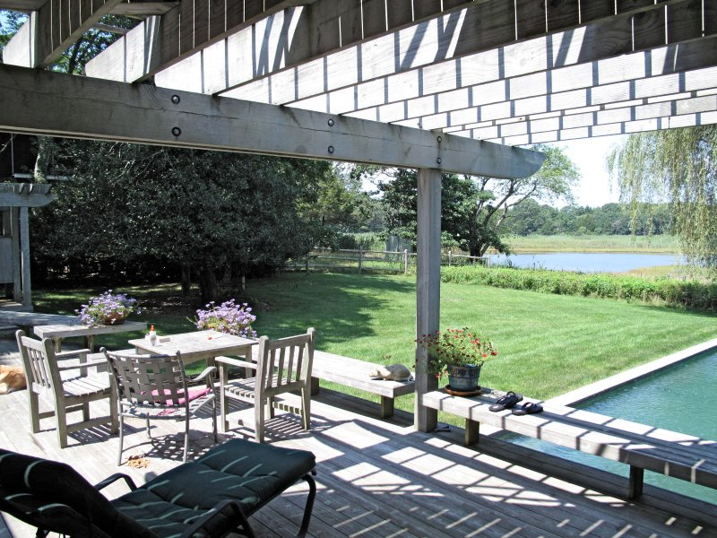 Disfrutar de comer o tomar el sol en la terraza trasera con vistas a la piscina y un estanque. Amplia zona de descanso y ducha cerrada.