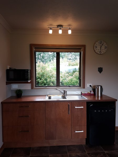 Kitchen with Kettle, toaster, microwave, electric frying pan, coffee plunger, tea pot.