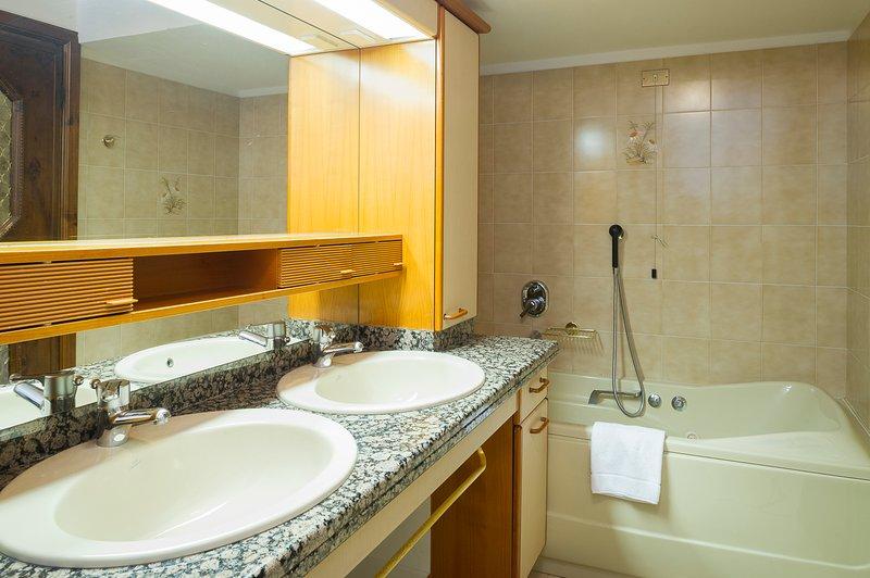 Salle de bains avec double vasque, baignoire et douche