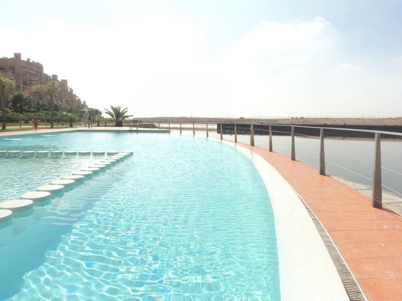 Apartamento con jardín privado frente al lago. Piscina y Golf, holiday rental in Alhama de Murcia