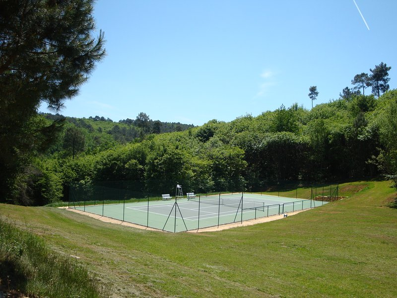 Guests can play a game of tennis in a beautiful green setting