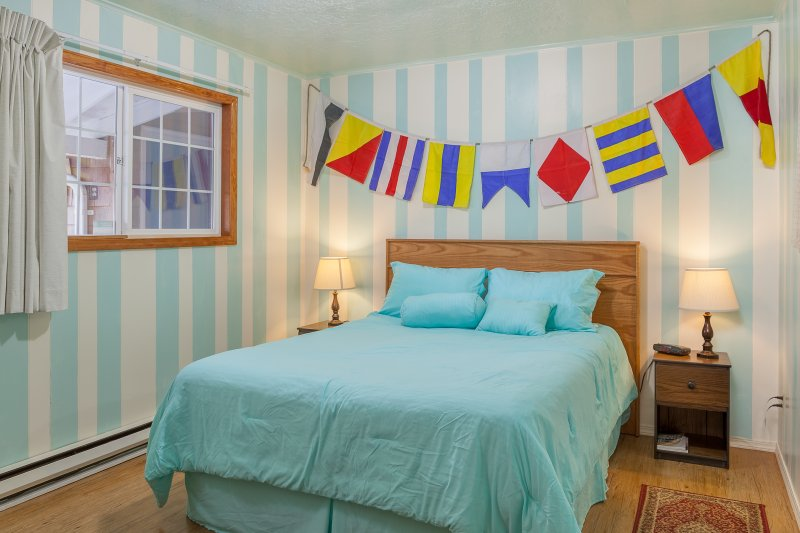 Queen bed in nautical themed bedroom