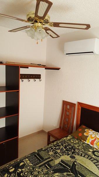 Camera da letto con ventilatore a soffitto e il centro climatico, letto matrimoniale e armadi.