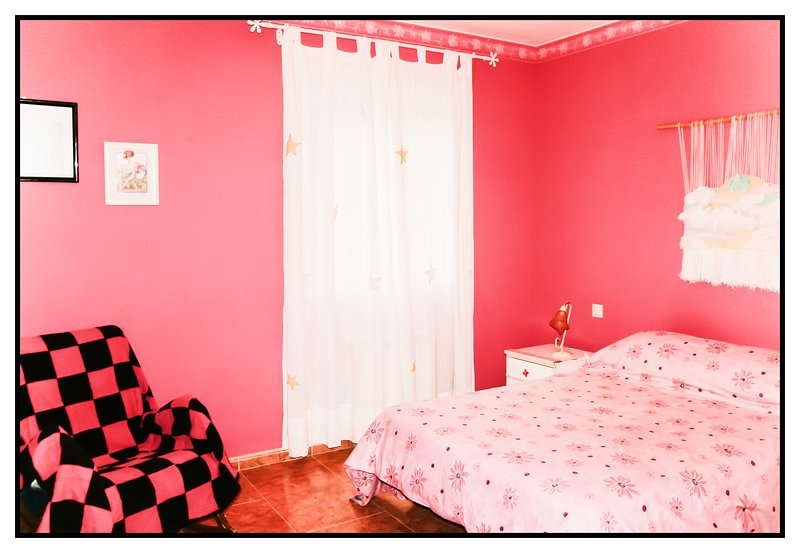 Fuchsia pink room with double bed, small table and rocking chair