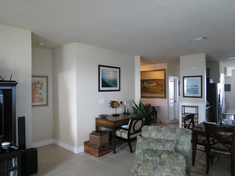 Main living area bright and clean with large TV, ample seating, access to balcony, open