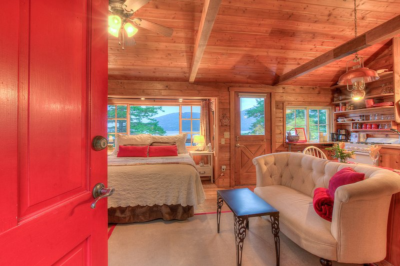 Isle Dream Cottage - A welcoming red door opens into a cozy interior with bed in window.