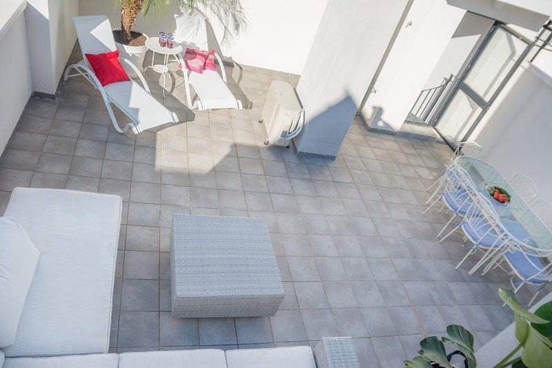 Terrasse privée: transats, table avec 6 chaises et un grand canapé