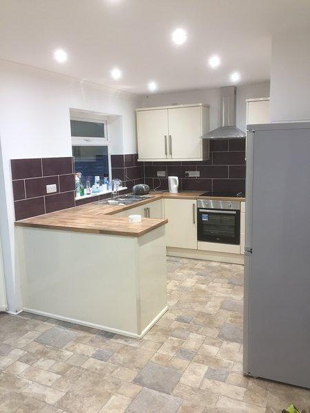 New kitchen with cooker dishwasher washing machine kettle toaster Microwave large fridge freezer.