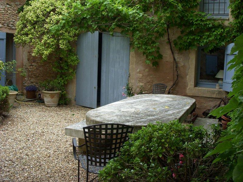 Vista de la sala de jardín de la puerta. el jazmín en el enrejado está en la floración