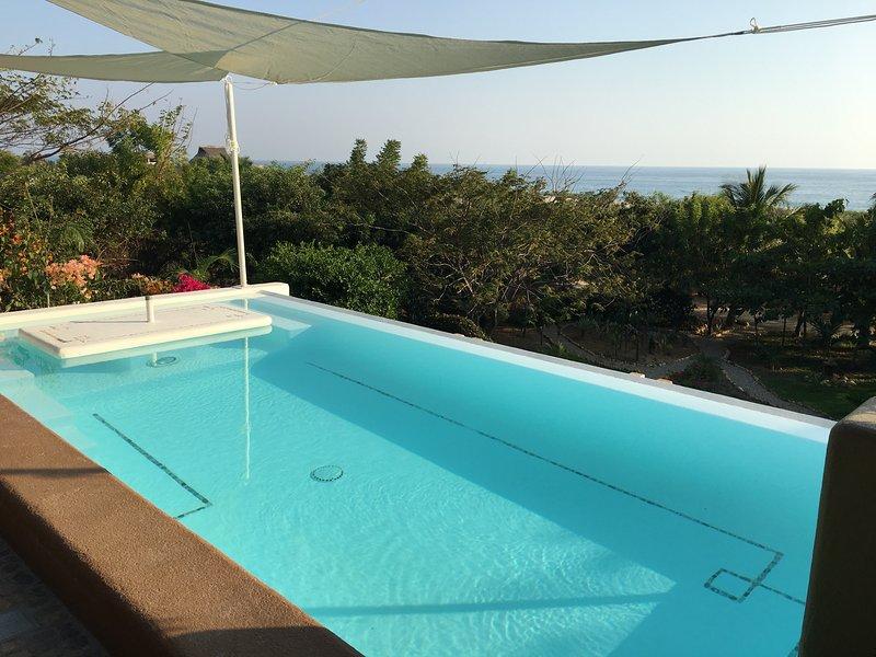 piscina no andar de cima, com jardins mesa com vista para o mar e