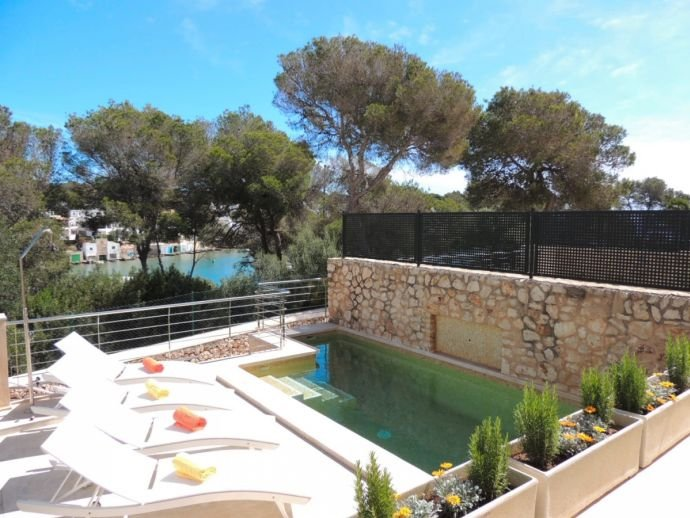 Pool area with comfortable sun loungers and views to the Marina