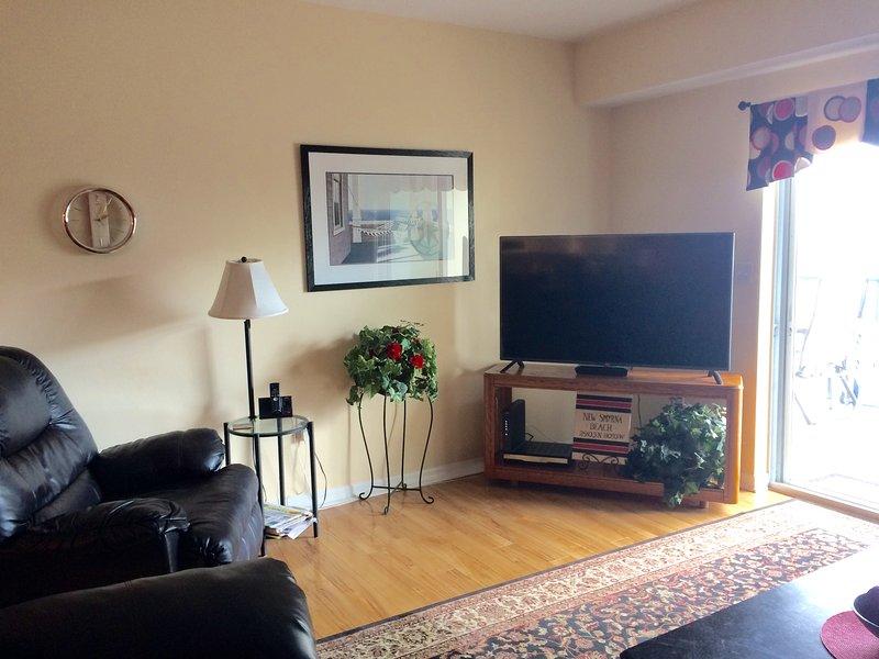 """sala de estar con TV de pantalla plana de 55"""""""